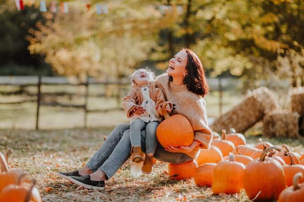 Giovane donna con sua figlia seduta sulle zucche