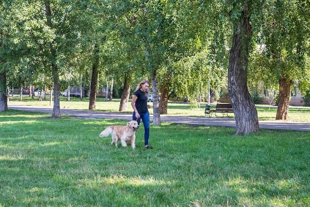 Giovane donna con il suo cane da riporto all'aperto.