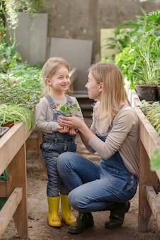 Una giovane donna con la sua piccola figlia sta piantando una pianta in un vaso in primavera in una serra.