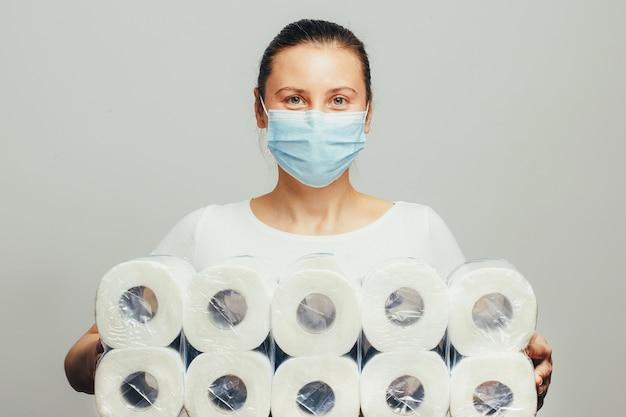 Giovane donna con tiene molti pacchetti di carta igienica.