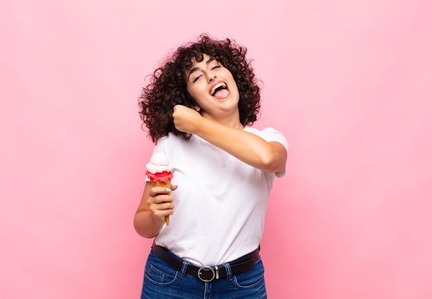 Giovane donna con un gelato che si sente felice, positiva e di successo, motivata quando affronta una sfida o celebra buoni risultati