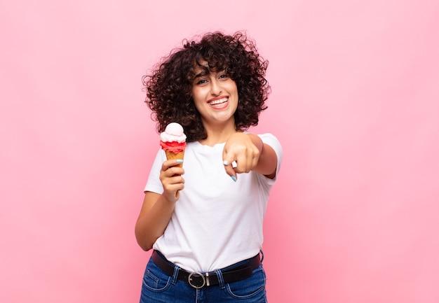 Giovane donna con un gelato che punta alla telecamera con un soddisfatto