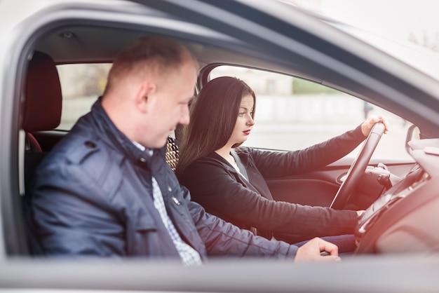 Giovane donna con istruttore seduto in macchina