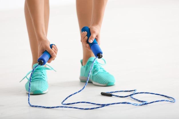 Giovane donna con salto con la corda al chiuso