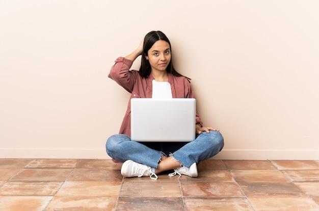 Giovane donna con un laptop seduto sul pavimento in posizione posteriore e pensare