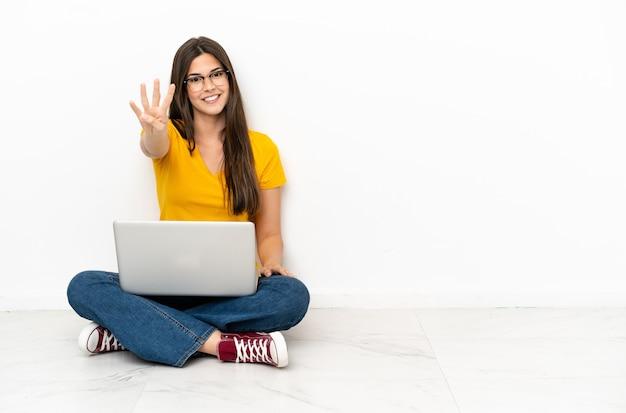 Giovane donna con un laptop seduto sul pavimento felice e contando quattro con le dita