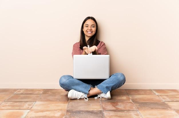 Giovane donna con un laptop seduto sul pavimento tenendo copyspace immaginario sul palmo per inserire un annuncio