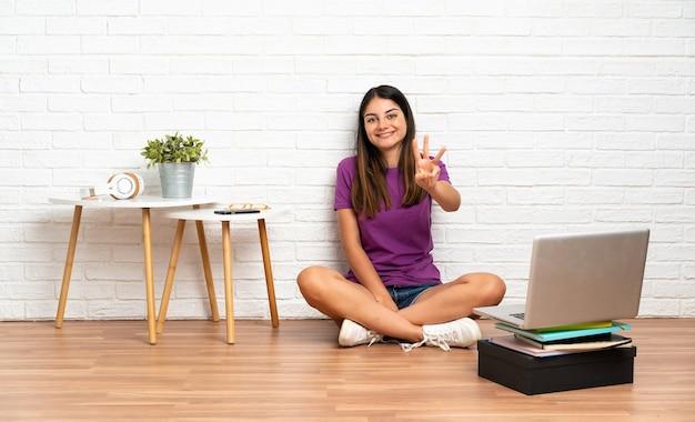 Giovane donna con un laptop seduto sul pavimento in casa felice e contando tre con le dita