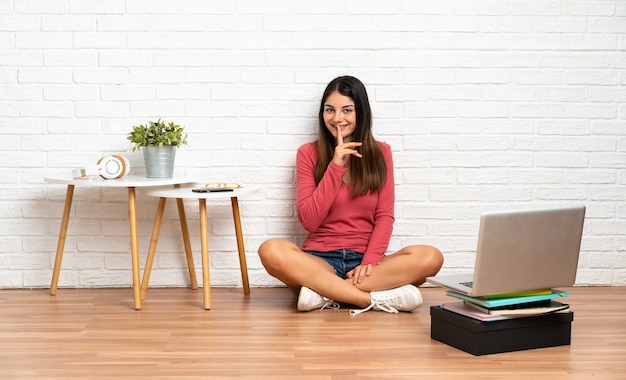 Giovane donna con un laptop seduto sul pavimento in interni che mostra un segno di silenzio gesto mettendo il dito in bocca