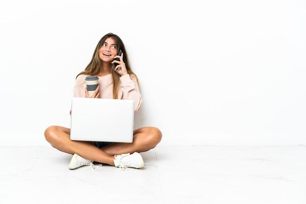 Giovane donna con un laptop seduto sul pavimento isolato su sfondo bianco tenendo il caffè da portare via e un cellulare