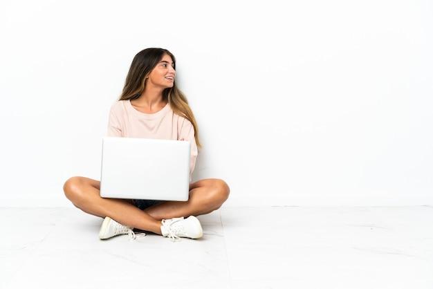 Giovane donna con un computer portatile seduto sul pavimento isolato su sfondo bianco che guarda di lato