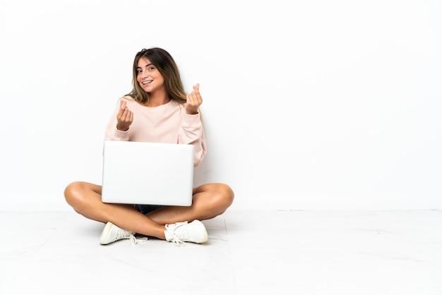 Giovane donna con un computer portatile che si siede sul pavimento isolato su fondo bianco che fa il gesto dei soldi
