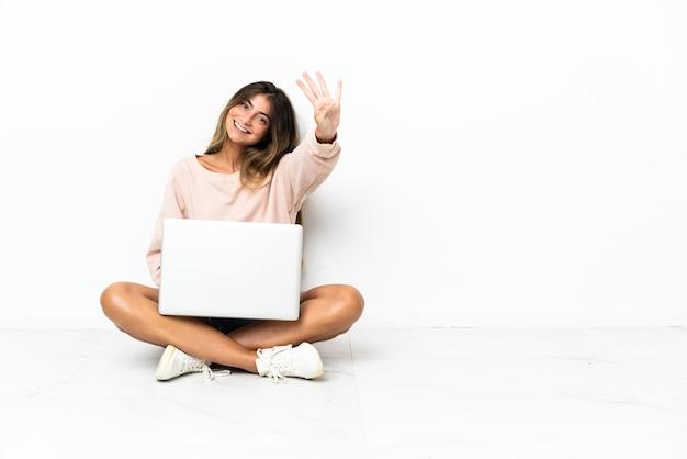Giovane donna con un laptop seduto sul pavimento isolato su bianco felice e contando quattro con le dita