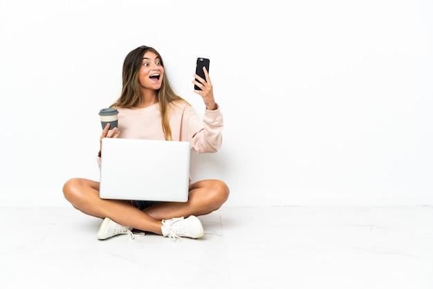 Giovane donna con un computer portatile seduto sul pavimento isolato su bianco tenendo il caffè da portare via e un cellulare
