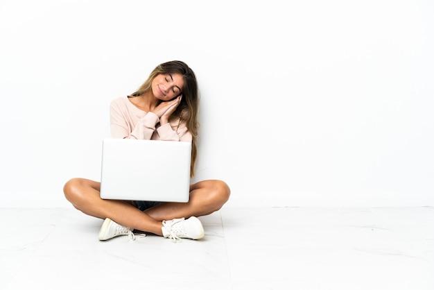 Giovane donna con un computer portatile che si siede sul pavimento isolato sulla parete bianca che fa gesto di sonno nell'espressione dorable