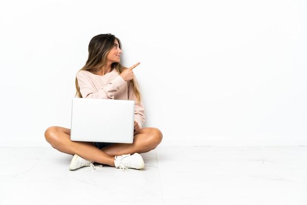 Giovane donna con un computer portatile seduto sul pavimento isolato sul muro bianco che punta indietro con il dito indice