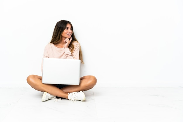 Giovane donna con un computer portatile che si siede sul pavimento isolato sulla parete bianca che pensa un'idea mentre osserva in su