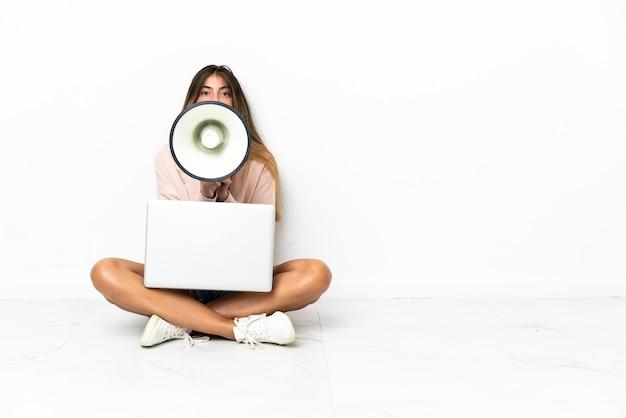 Giovane donna con un computer portatile che si siede sul pavimento isolato