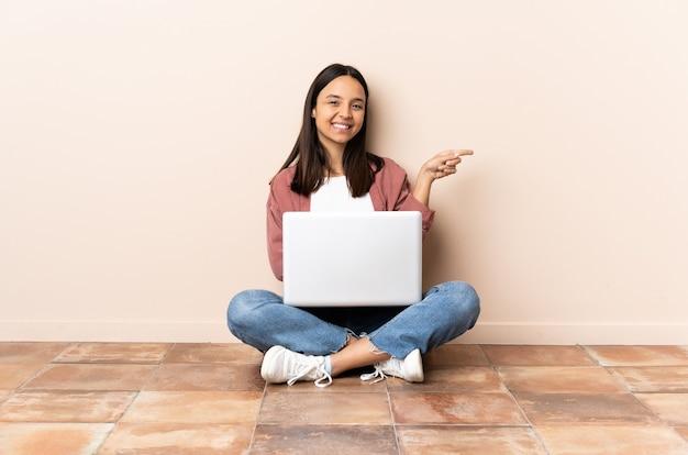 Giovane donna con un laptop seduto sul pavimento che punta il dito di lato