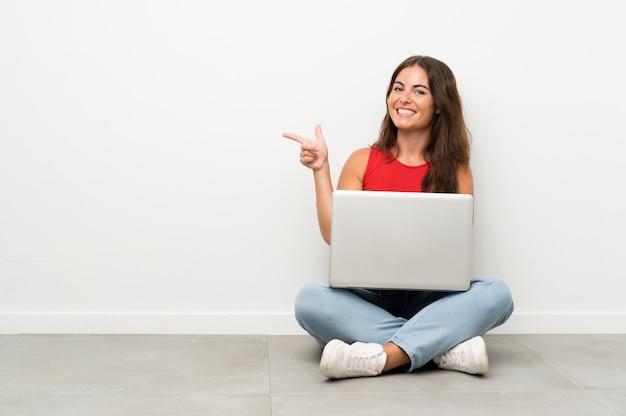 Giovane donna con un computer portatile che si siede sul pavimento che punta il dito verso il lato