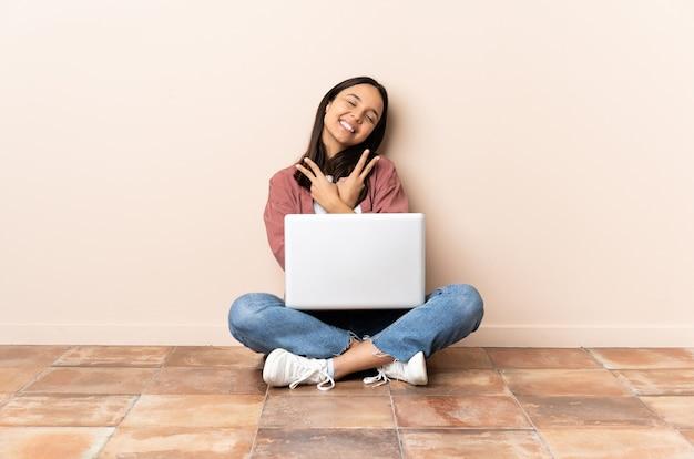 Giovane donna con un laptop seduto sul pavimento sorridendo e mostrando il segno di vittoria