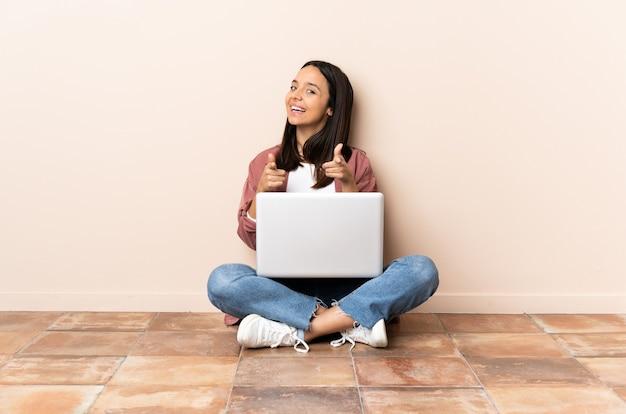 Giovane donna con un computer portatile che si siede sul pavimento sorpreso e che indica davanti