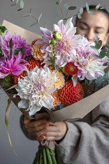 Giovane donna con un grande mazzo festivo di crisantemi