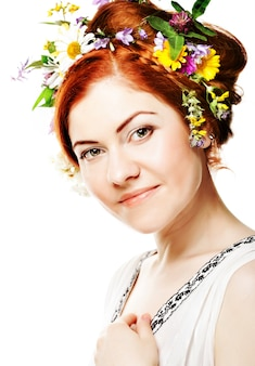 Giovane donna con grande acconciatura e fiori tra i capelli.