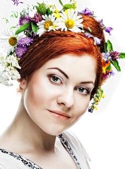 Giovane donna con grande acconciatura e fiori tra i capelli