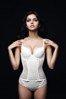 Giovane donna con lingerie davanti a sfondo bianco. donna sexy. bella donna felice. intimo pubblicitario. l'immagine del modello pubblicizza lingerie sexy. trucco di lusso. perfetto corpo sottile. capelli lunghi.