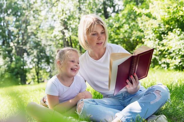 Una giovane donna con una piccola figlia si trova nel parco sull'erba e legge un libro. bella bionda con le lentiggini sul viso. campeggio in una soleggiata giornata estiva.
