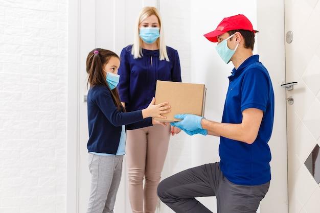 Giovane donna con figlia piccola che indossa una maschera medica che riceve cibo ordinato dall'uomo delle consegne al chiuso. prevenzione della diffusione del virus