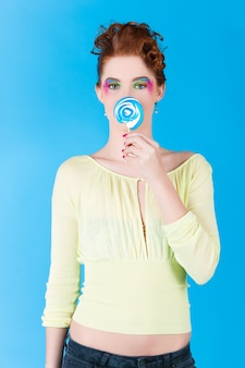 Giovane donna con un lecca lecca o lecca lecca, ha un debole per i dolci