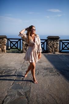 Una giovane donna con lunghi capelli biondi in un top e una gonna sta camminando in una giornata di sole estivo. la ragazza felice con un sorriso sul viso e con gli occhiali da sole sta camminando in una giornata di sole Foto Premium