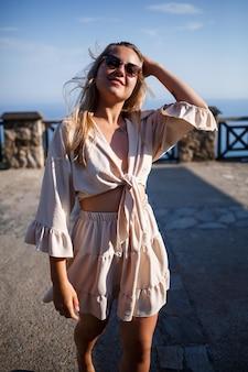 Una giovane donna con lunghi capelli biondi in un top e una gonna sta camminando in una giornata di sole estivo. la ragazza felice con un sorriso sul viso e con gli occhiali da sole sta camminando in una giornata di sole