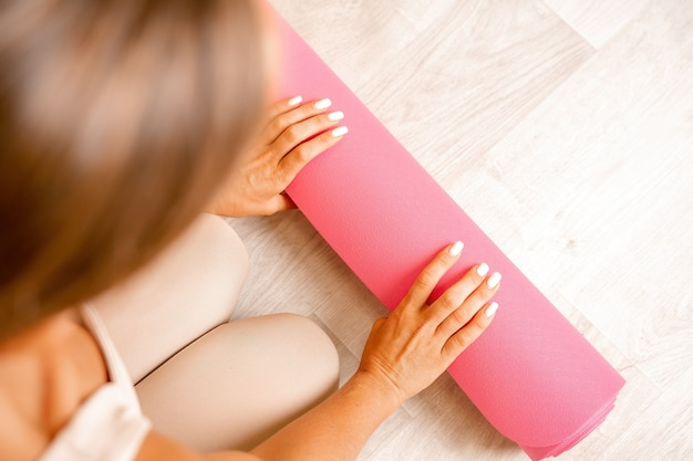 Giovane donna con capelli lunghi istruttore di fitness in abiti sportivi beige che si prepara per lo stretching e