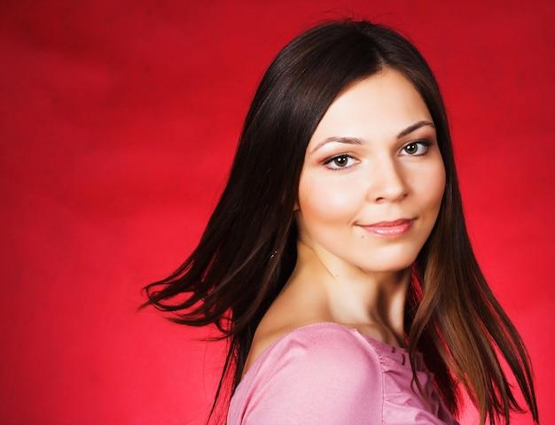 Giovane donna con capelli lunghi in posa in studio su superficie rossa. bellezza, moda.