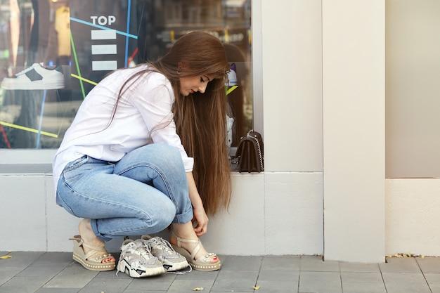 La giovane donna con i capelli lunghi si siede per allacciare la cinghia alla gamba delle sue scarpe