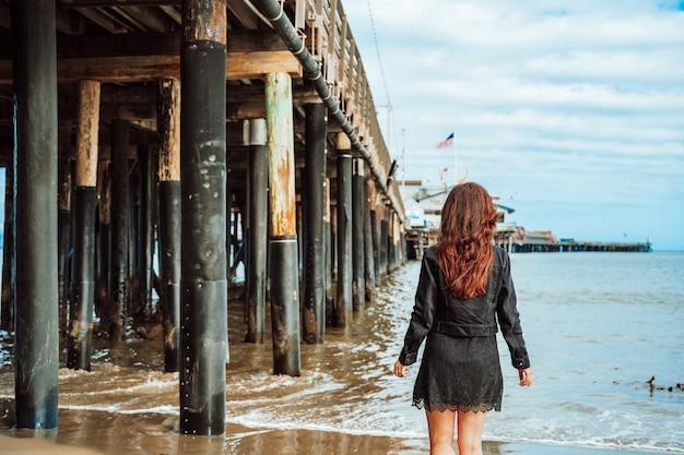 Giovane donna con i capelli lunghi si trova vicino al molo sulla spiaggia di santa barbara california usa