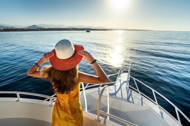 Giovane donna con i capelli lunghi che indossa un abito giallo e un cappello di paglia in piedi su uno yacht bianco