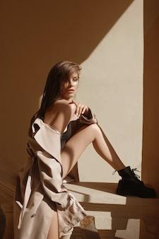 Giovane donna con gambe lunghe sexy che indossa un impermeabile in posa sulla strada della città