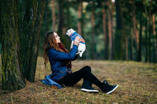 Giovane donna con una lunga seduta sul terreno oltre gli alberi nella foresta con il suo adorabile cucciolo di chihuahua nelle mani.