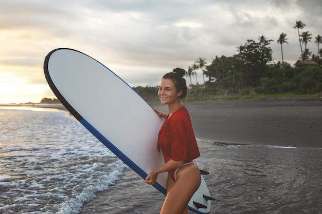 Giovane e donna con un longboard durante la sessione di surf sulla spiaggia