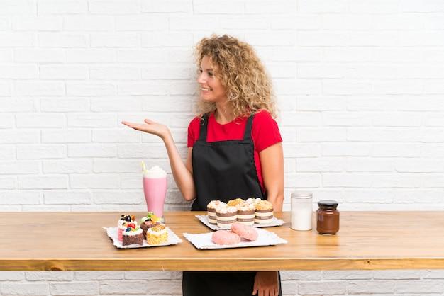 Giovane donna con tante mini torte diverse in un tavolo allungando le mani a lato per invitare a venire