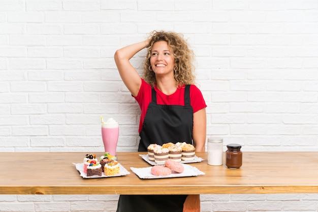 Giovane donna con un sacco di diverse mini torte in una risata della tabella