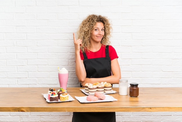 Giovane donna con un sacco di diverse mini torte in una tabella che punta con il dito indice un'ottima idea