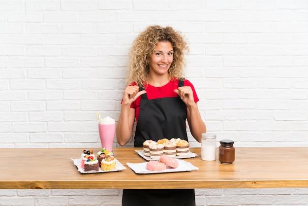 Giovane donna con tante mini torte diverse in un tavolo orgoglioso e soddisfatto