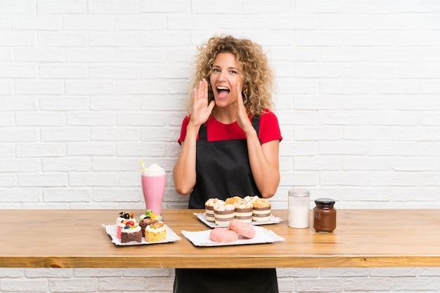 Giovane donna con un sacco di diverse mini torte in un tavolo che grida con la bocca spalancata