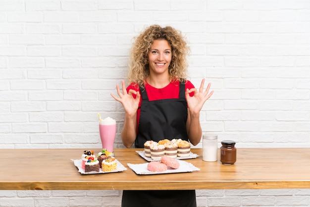 Giovane donna con un sacco di diverse mini torte in una tabella che mostra un segno ok con le dita