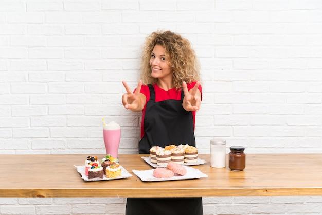 Giovane donna con un sacco di diverse mini torte in un tavolo sorridente e mostrando il segno della vittoria